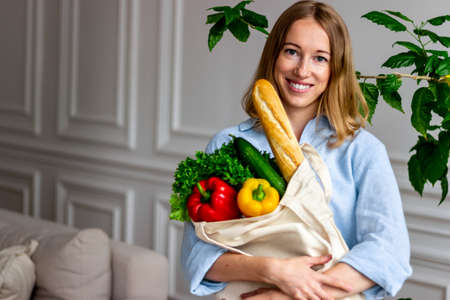 Smiling blond woman with grocery shopping bag full of vegetables