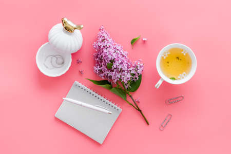 Lilas flowers bouquet with cup tea and notepad top view