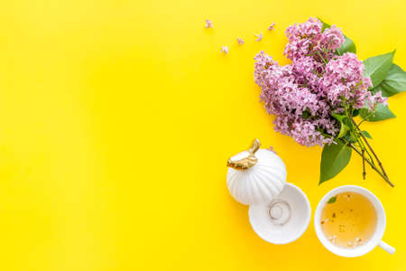 Lilas flowers bouquet with tea on working office table desk. Top view Banque d'images