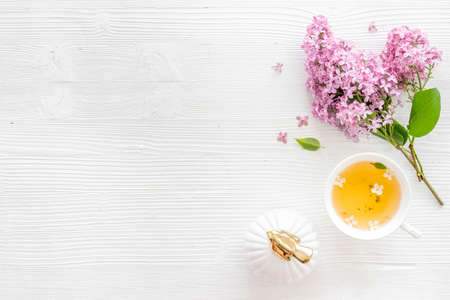 Flat lay of lilas flowers bouquet with cup tea on workspace