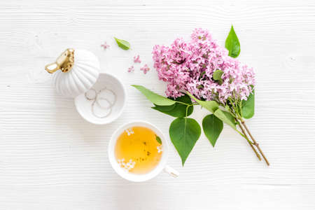 Flat lay of lilas flowers bouquet with cup tea on workspace Banque d'images