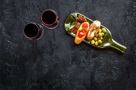 Toasts with prosciutto and tomatoes with red wine top view space for text