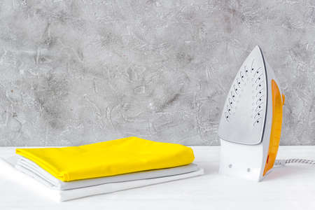 Ironing clothes with a yellow iron on board