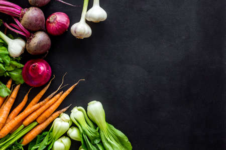 Flat lay of fresh vegetables and greenery on black table top-down copy space