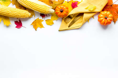 Thanksgiving flat lay with table setting leaves and pumpkins, overhead view
