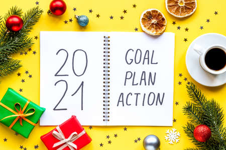 2021 New Year goals and plan with Christmas decorations and gift box. Overhead