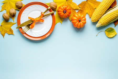 Thanksgiving holidays concept with dishes and pumpkins, top view