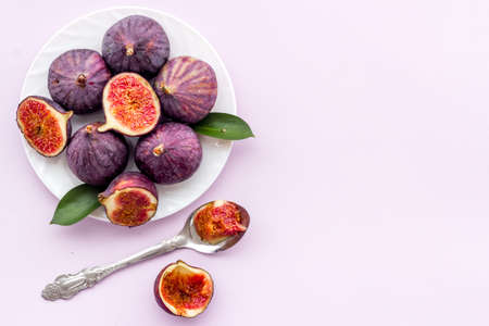 Fresh whole and sliced figs on a plate with green leaves. Top view 版權商用圖片