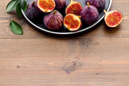 Fresh figs in a bowl with green leaves. Top view