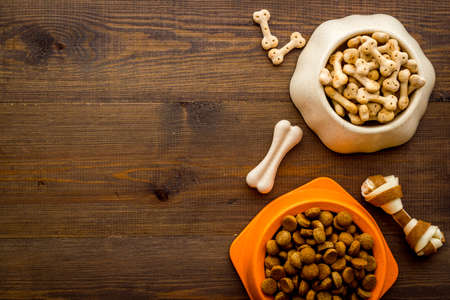 Dry dog food in bowls with bones, top view, copy space