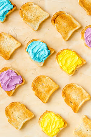 Pattern of toast bread with colored cheese spread. Layout top view 版權商用圖片