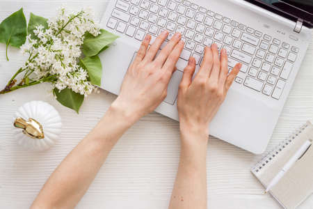 Female hands with laptop. Workplace with jasmine flowers top view 版權商用圖片