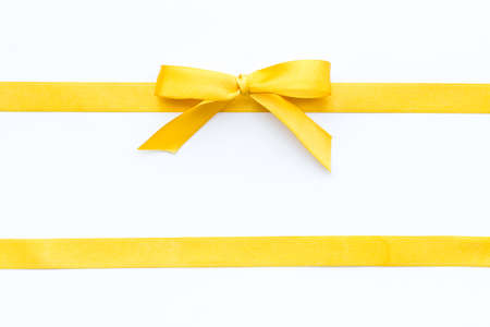 Yellow ribbon bow isolated on white background, top view, copy space Stockfoto