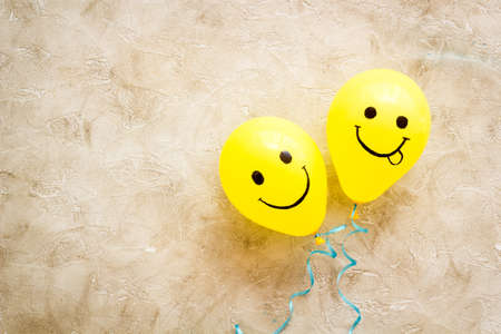 Positive emotions set. Happy and winking emoticons painted on colored balloons