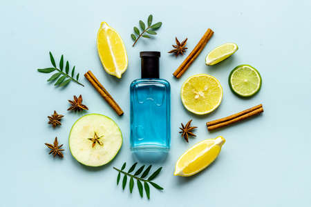 Flat lay of men perfume with flowers and citrus. Top view
