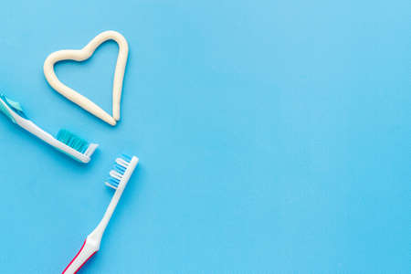 Heart shape of toothpaste with toothbrush, top view. Oral care and hygiene