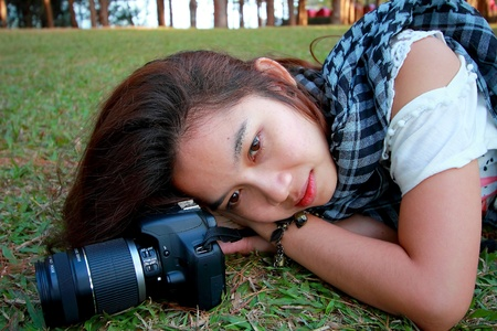 Woman is lay down on the ground with her camera