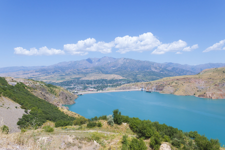 The dam is high in the mountains. Below, in the distance is a small town. Stock Photo