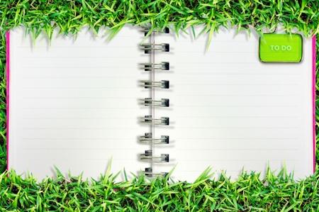 lege pagina van nota boek over gras en wit isolaat Stockfoto