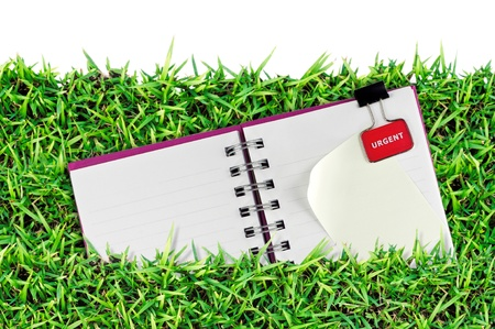 blank page of note book on grass and white isolate photo
