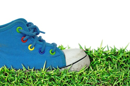 old, dirty sneakers over spring green grass photo