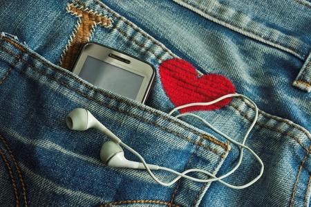 MP3-speler en mobiele telefoon in een zak jeans Stockfoto