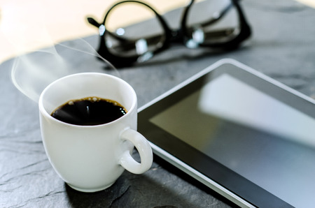 Coffee cup ,glasses and tablet on stone table photo