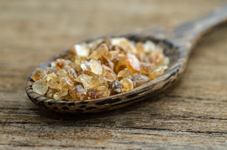 close up of crystalline sugar and wooden spoon on wooden table   Selective Focus photo