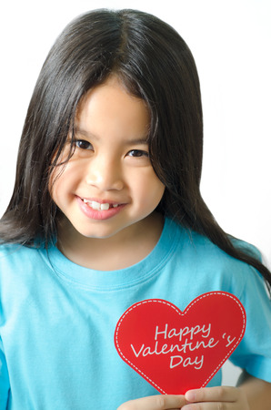 asien: Color photo of a 7 year old, asien black haired girl  holding an heart-shaped