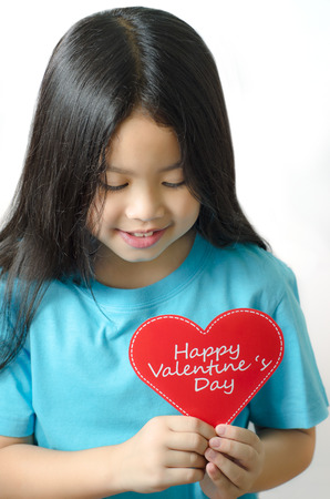 asien: Color photo of a 7 year old, asien black haired girl  holding an heart-shaped Stock Photo