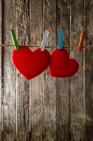 Cute big red heart hanging on the clothesline. On old wood background. photo