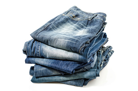 Folded Old Blue Jeans Isolated on a white. Clipping path included. Фото со стока