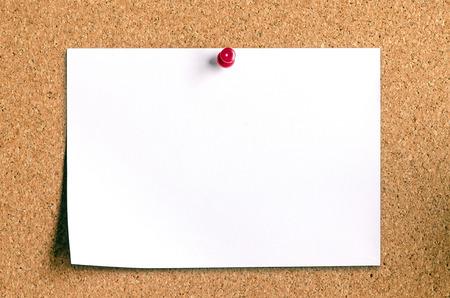 closeup of blank note paper on cork board