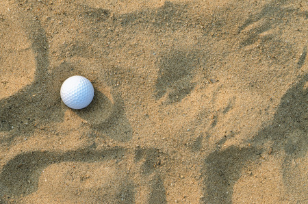 A golf ball on the sand ; top view Imagens