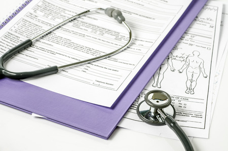stethoscope resting on a sheet of medical lab test results, with patient file and x-ray or mri film
