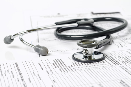 stethoscope resting on a sheet of medical lab test results photo