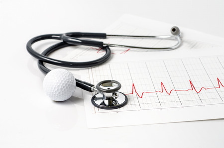 stethoscope and golf ball on white background photo