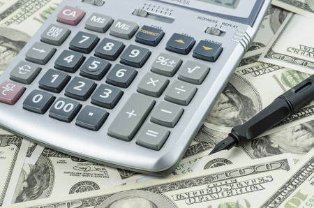 international bank account number: Pen and Calculator on a background of american dollar bills Stock Photo