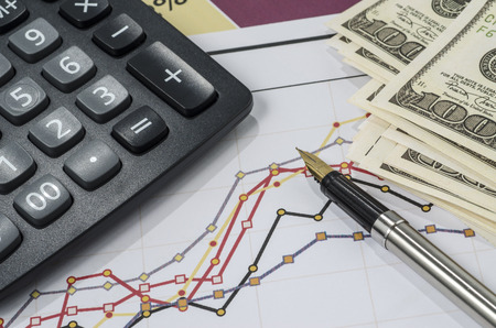 fountain pen and calculator on the financial graph Foto de archivo