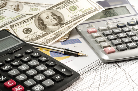 Fountain pen and calculator on the financial graph photo