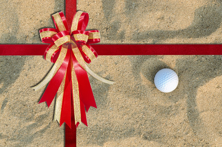 christmas golf: Red Ribbon on A golf ball on the sand for background ; top view Stock Photo