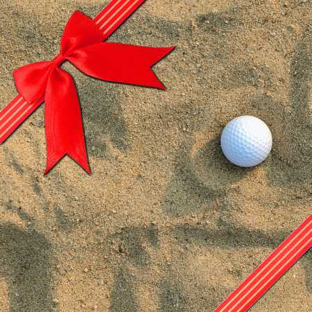 Red  Cross ribbon bow on a  golf ball on the sand for background photo