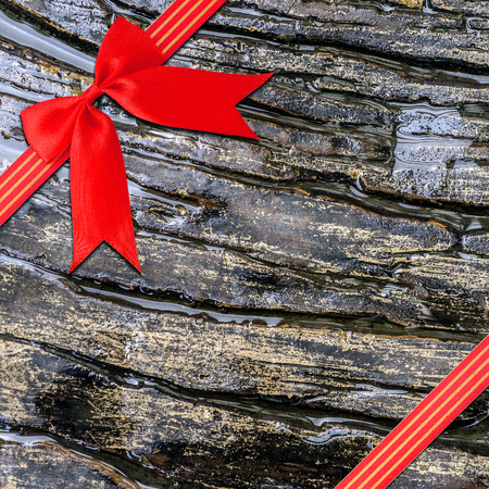 spot lit: Red  Cross ribbon bow on Texture backgronud