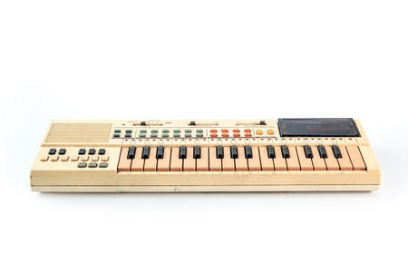 Old vintage synthesizer isolated on white photo