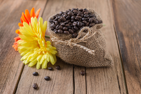 sack bag full of roasted coffee beans on wooden background with sunflower