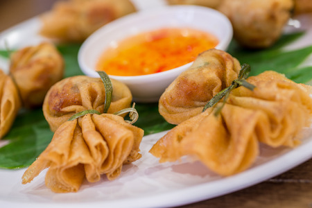 Oriental fried wonton filled with prawns and vegetables served with sweet chilli and dumpling sauce. photo