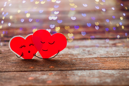 Red Valentine hearts smily and hug on old rustic wooden background 스톡 콘텐츠