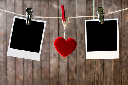 Two blank instant photos hanging on the clothesline with  red heart photo