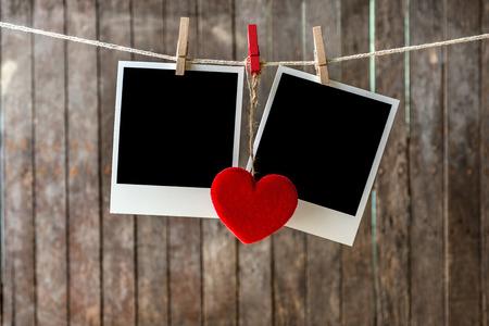 Twee lege instant foto's opknoping op de waslijn met rood hart Stockfoto