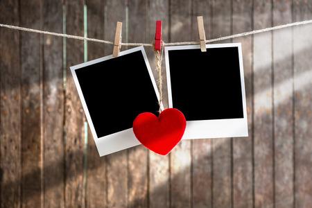 Twee lege instant foto's opknoping op de waslijn met rood hart, .Clipping pad voor insert Photo